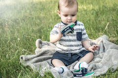 A cute baby sitting and playing with his shoe in nature in a summer park on grass. A cute baby sitting and playing with his shoe in a summer park on grass royalty free stock photography