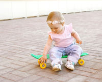 Cute baby sitting on the skateboard outdoors Royalty Free Stock Photography
