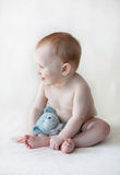 Cute baby sitting up with a toy Royalty Free Stock Images