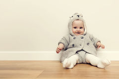 Cute baby sitting on wooden floor. Smiling and wearing cozy sweater. Vintage Royalty Free Stock Photography