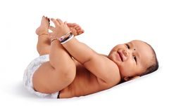 Cute baby sleeping on bed holding his feet and laughing, Pune, Maharashtra.  stock photography