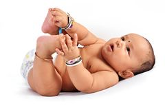 Cute baby sleeping on bed holding his feet and laughing, Pune, Maharashtra stock photos