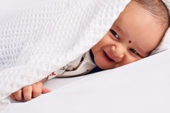 Cute baby sleeping on bed on stomach laughing, Pune, Maharashtra stock photos