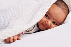 Cute baby sleeping on bed on stomach laughing, Pune, Maharashtra stock image
