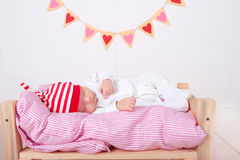Cute baby sleeping. Cute baby boy sleeping on soft bed with valentines hearts on background Stock Photography
