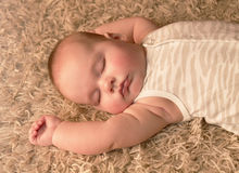 Cute baby sleeping on carpet Stock Photography