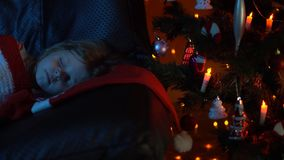 A little girl is sleeping on a sofa under a rug at a Christmas tree at night. A cute baby is sleeping on a couch under a striped red white plaid beside is a stock video