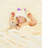 Cute baby sleeping with teddy bear on white bed home Stock Image