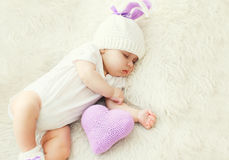 Cute baby sleeping on white bed at home with knitted pillow heart Stock Photos