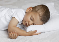 Cute child is sleeping in bed. Cute baby sleeping with a white shirt on a white bed stock images
