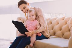 Cute baby smiling while a babysitter showing her lovely pictures. Progressive babysitter. Lovely baby girl sitting on the knees of a babysitter and looking at royalty free stock photo