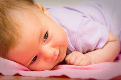 A cute baby smiling on a bed Royalty Free Stock Image