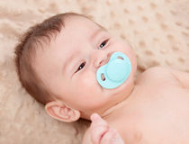 Cute baby smiling with blue pacifier Stock Photography