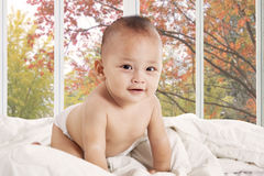 Cute baby smiling at camera in bedroom Stock Images