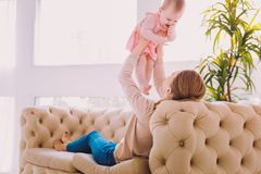 Cute baby smiling while her mother holding her in the air. Happy childhood. Cheerful emotional child smiling while a kind attentive mother holding her baby in stock images