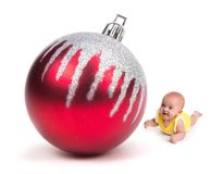 Cute Baby smiling at a Huge Christmas Ornament on white stock image