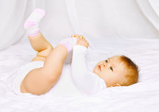 Cute baby in socks lying on the bed and holding legs Royalty Free Stock Photos
