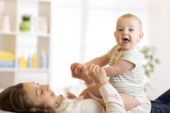 Cute baby son sitting on his happy mom lying on floor at home. royalty free stock images