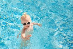 Cute baby splashing in the pool in the summer. Cute little baby in sunglasses swimming in the pool and waving his hand. Place for text. The view from the top Royalty Free Stock Images