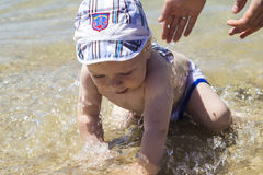 Cute baby is splashing in the sea, the hands of his father insur. Cute baby is splashing in the sea, hands of his father insure him Stock Image