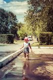 Cute baby sports and runs through the puddles on a summer sunny royalty free stock image