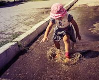 Cute baby sports and runs through the puddles on a summer sunny stock photos