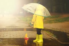 Happy child is playing in a puddle on a summer rainy day. a boy in a yellow raincoat walks in the park. royalty free stock photography