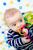 Cute baby in striped clothes lying down on a blanket Royalty Free Stock Photography