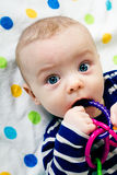 Cute baby in striped clothes lying down on a blanket Stock Photo