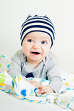 Cute baby in striped hat lying down on a blanket Royalty Free Stock Images