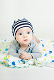 Cute baby in striped hat lying down on a blanket Royalty Free Stock Photos