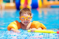 Cute baby swimming in pool with inflatable arm rings. Cute baby boy swimming in pool with inflatable arm rings stock photography