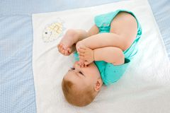 Cute baby taking feet in mouth. Adorable little baby girl sucking foot. Cute baby taking feet in mouth. Adorable little baby girl sucking own foot Stock Photos