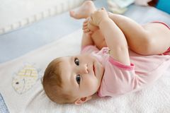 Cute baby taking feet in mouth. Adorable little baby girl sucking foot. Cute baby taking feet in mouth. Adorable little baby girl sucking own foot Royalty Free Stock Images