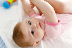 Cute baby taking feet in mouth. Adorable little baby girl sucking foot. Cute baby taking feet in mouth. Adorable little baby girl sucking own foot Royalty Free Stock Image