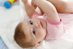 Cute baby taking feet in mouth. Adorable little baby girl sucking foot. Cute baby taking feet in mouth. Adorable little baby girl sucking own foot Stock Images