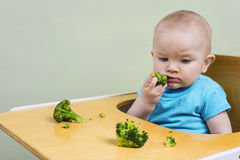 Cute baby tasting broccoli Royalty Free Stock Photography