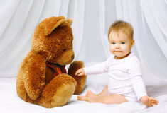 Cute baby and teddy bear Stock Images