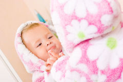 Cute baby with terry bathrobe looking at mirror Stock Photo