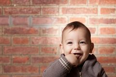 Cute Baby thinking on a bricks background Stock Images