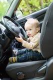 Cute baby  toddler boy in a car. Cute baby  toddler boy behind wheel of car Stock Photo