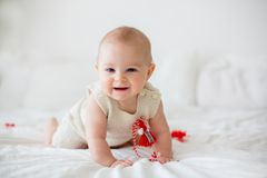Cute baby toddler boy, playing with white and red bracelets. Martenitsa, white and red strains of yarn, Bulgarian folklore tradition, welcoming spring in March Stock Image