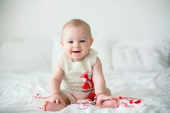 Cute baby toddler boy, playing with white and red bracelets. Martenitsa, white and red strains of yarn, Bulgarian folklore tradition, welcoming spring in March Stock Photography