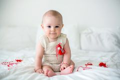 Cute baby toddler boy, playing with white and red bracelets. Martenitsa, white and red strains of yarn, Bulgarian folklore tradition, welcoming spring in March Royalty Free Stock Images
