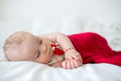 Cute baby toddler boy, sleeping with white and red bracelet. Martenitsa, white and red strains of yarn, Bulgarian folklore tradition, welcoming spring in March stock photos
