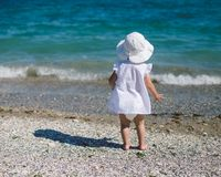 Cute baby toddler girl on the beach. Summer sunset on the beach Stock Photo