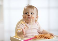 Cute baby toddler girl eating spaghetti with tomato sauce sitting in a white sunny room with big window stock photos