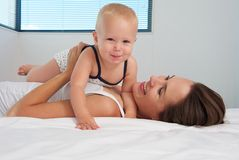 Cute baby together with happy young mother Stock Images