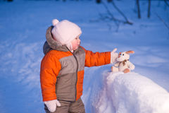 Cute baby touch toy dog on snow Royalty Free Stock Photos
