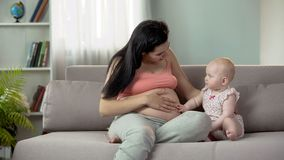 Cute baby touching mommy pregnant belly, expecting little sister or brother. Stock photo royalty free stock images